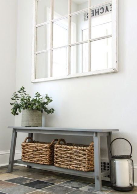 a grey vintage bench with an additional shelf and baskets for storing various things and shoes