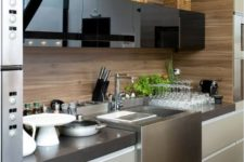 06 a minimalist kitchen with glossy black and matte off-white cabinets plus a plywood backsplash