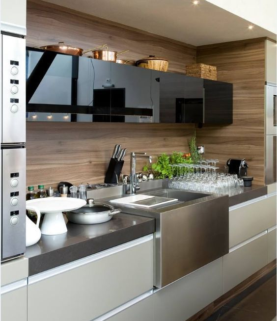 a minimalist kitchen with glossy black and matte off-white cabinets plus a plywood backsplash
