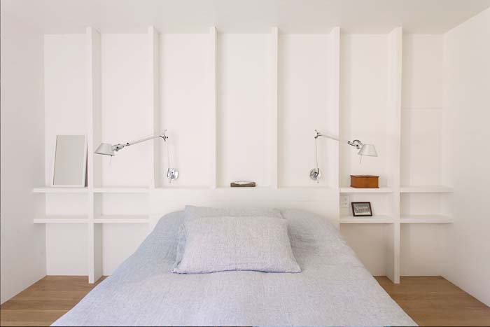 The master bedroom features white walls with shelves, a comfy bed and some sconces