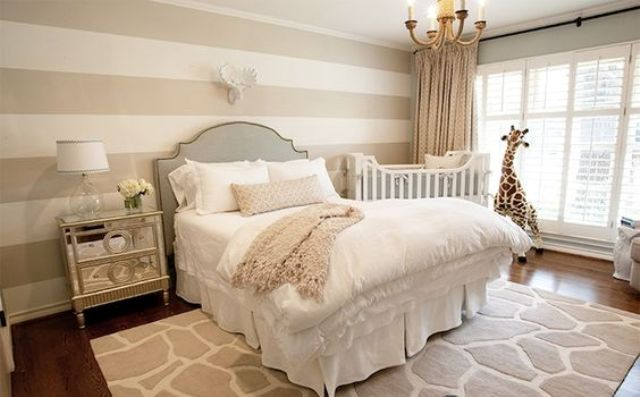 a chic space with a glam feel and a crib by the window, a giraffe toy and a rug are matching