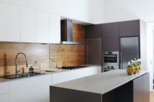 07 a minimalist kitchen with white sleek cabinets and a warm wood panel backsplash plus an additional glass screen in the cooker zone