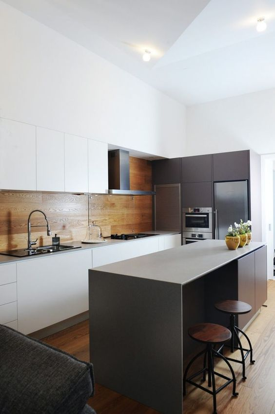 a minimalist kitchen with white sleek cabinets and a warm wood panel backsplash plus an additional glass screen in the cooker zone