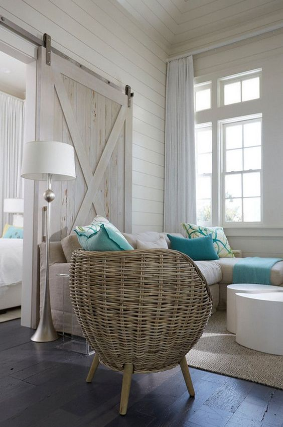 a whitewashed barn door is a part of decor and perfectly matches a coastal space