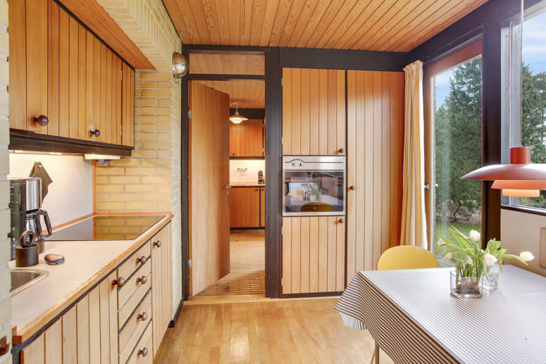 The kitchen is a separate room with its own breakfast space, there are wooden cabinets and a glazed wall