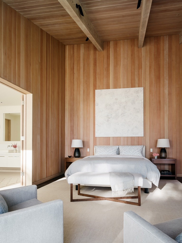 The master bedroom features comfortable contemporary furniture and much wood that clads the walls and a high ceiling