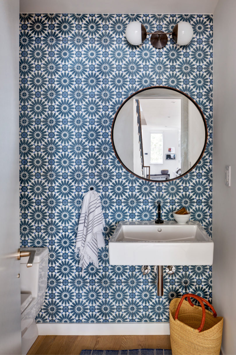 The powder room shows off a statement wall with gorgeous blue printed tiles and a round mirror