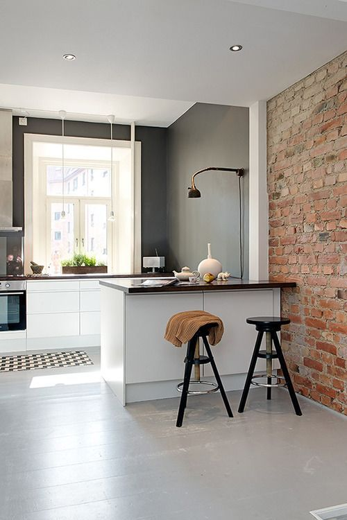 a small contemporary kitchen nook separated from the rest of the space with a kitchen island