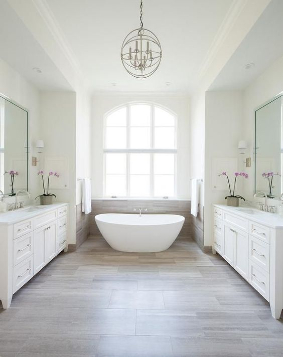 a white bathroom is accented with wood and the backsplash saves the window and makes the bathroom feel spacious