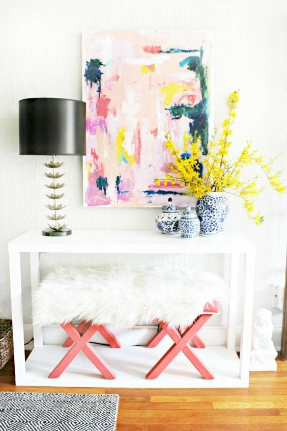 a white console, pink and fur stools and a bright abstract artwork plus bold flowers for a cool look