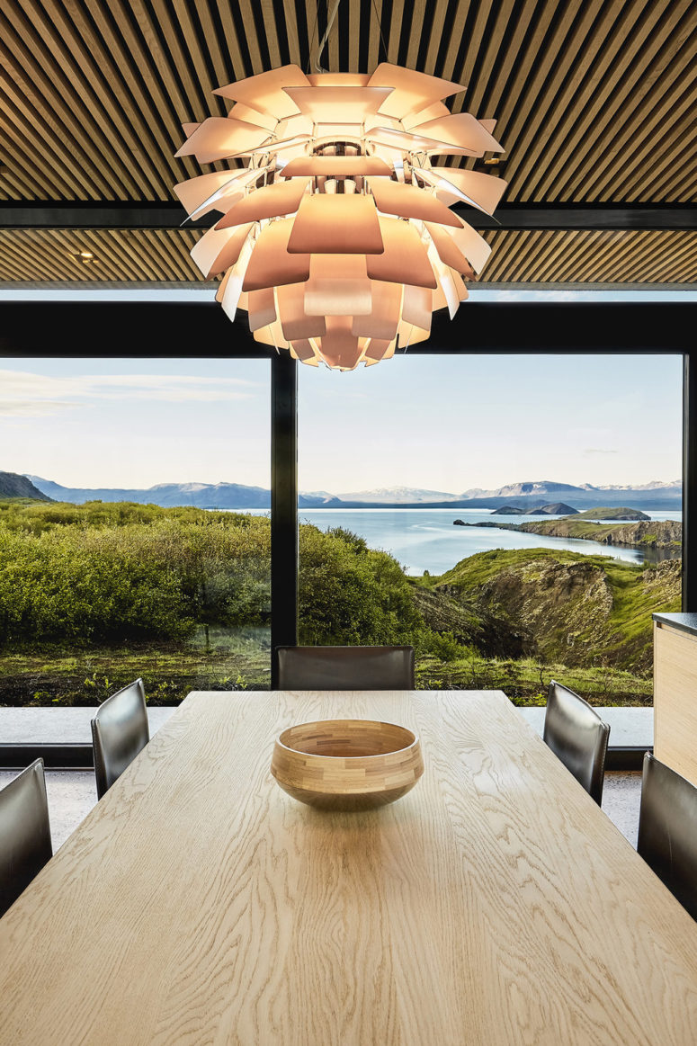 The dining space is done with black leather chairs and a light-colored wooden table and look at those views