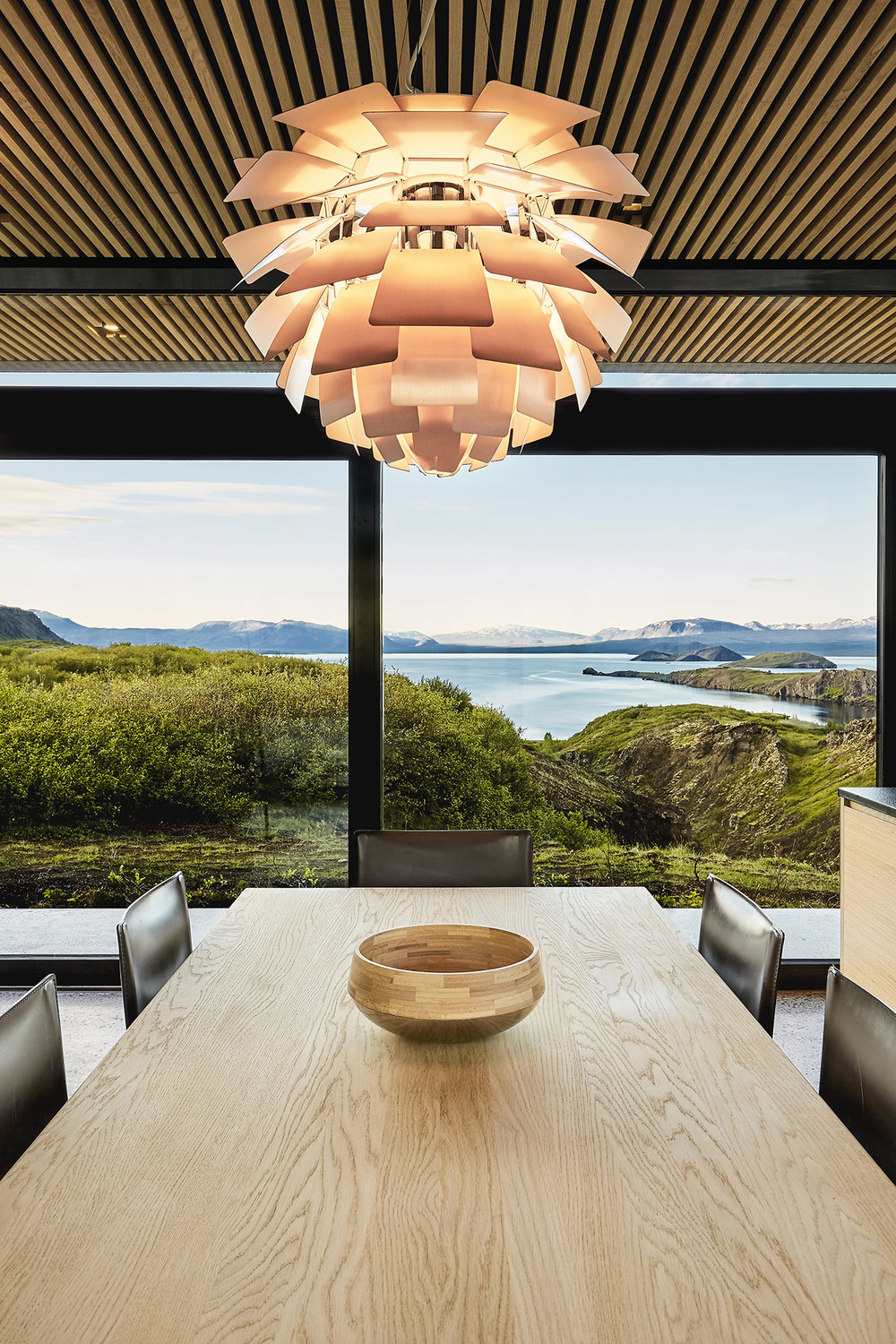 The dining space is done with black leather chairs and a light colored wooden table and look at those views
