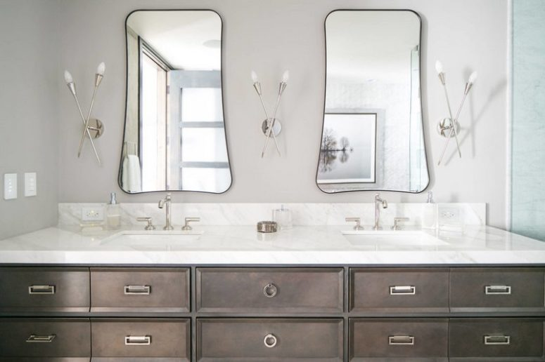 You may see a large double vanity, eye-catchy shaped mirrors and creative wall lamps