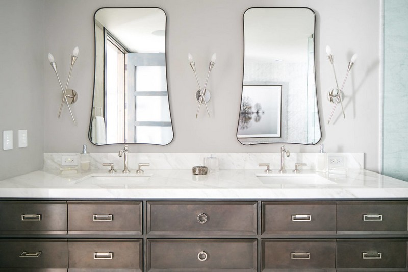 You may see a large double vanity, eye catchy shaped mirrors and creative wall lamps
