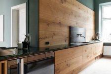 09 a modern kitchen with sleek walnut cabinets and a backsplash and dark green walls