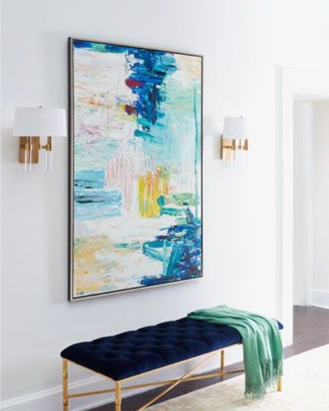an oversized bright watercolor brushstroke artwork and a matching navy and copper upholstered bench