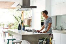 09 bring an industrial feel to your modern space with a concrete kitchen island and a metal hood