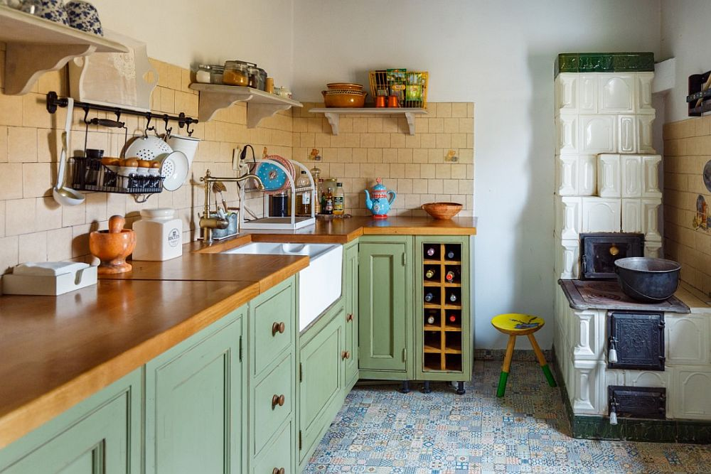 The kitchen features grass green cabinets with wooden countertops and a tan tile backsplash
