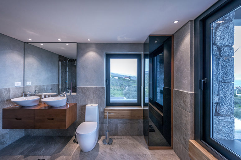 The master bathroom is done with concrete, stone-like tiles and wooden pieces to make it warmer
