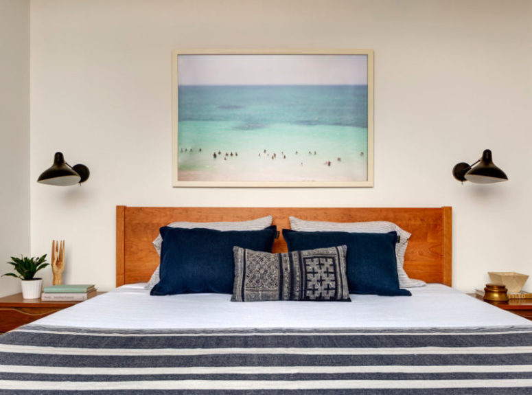 The master bedroom features a wooden bed, some nightstands and sconces and a gorgeous artwork from personal owners' photos