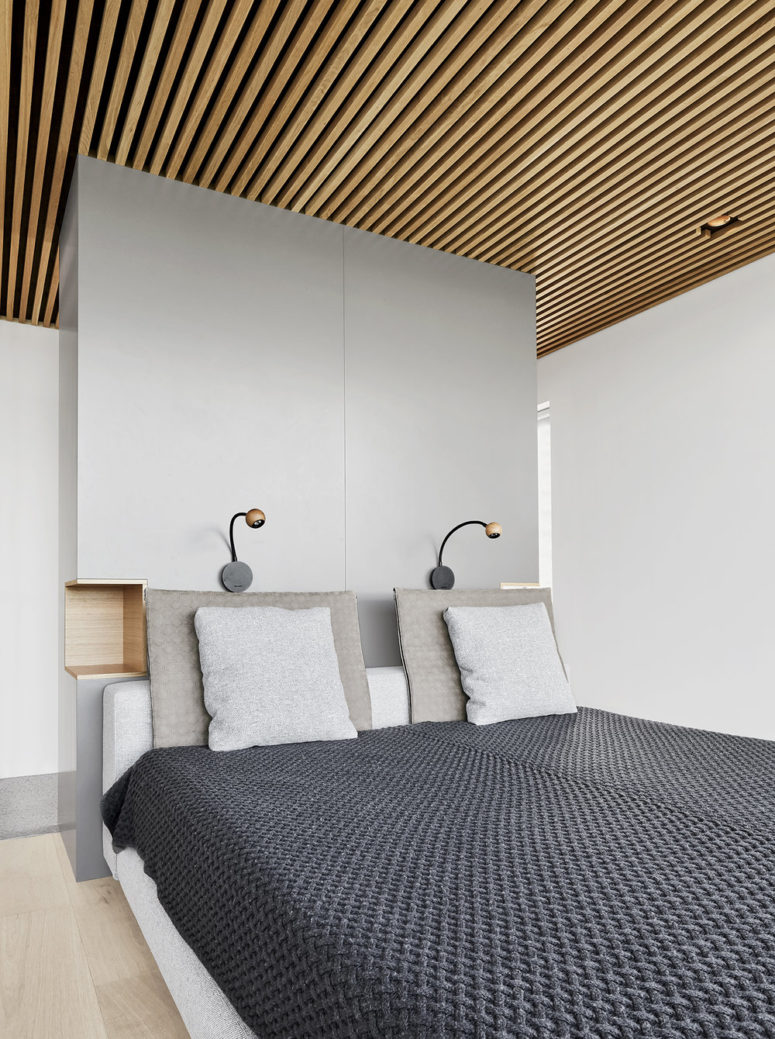 The master bedroom is done with an upholstered bed and a sleek grey headboard with built-in nightstands