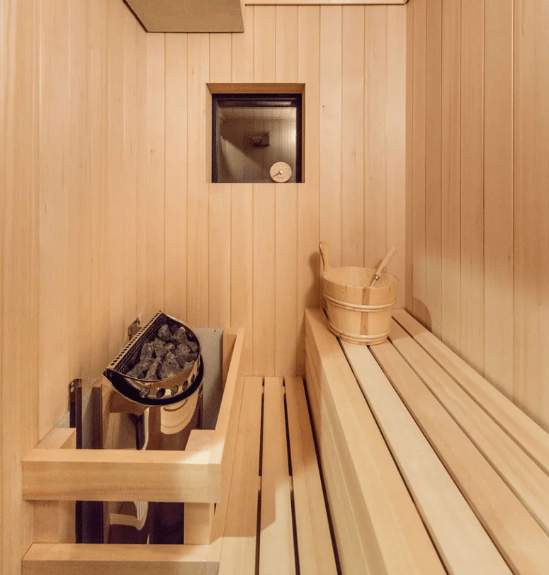 There's a sauna fully clad with light-colored wood and designed in minimalist style like the rest of the home