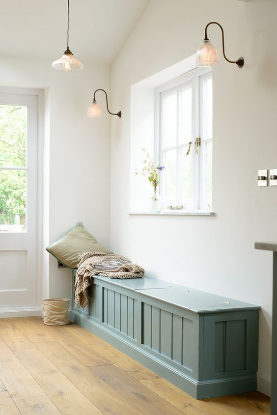 a blue farmhouse bench with much storage space inside for a vintage entryway