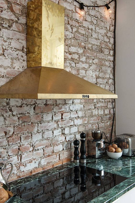 a gorgeous brass hood and a green marble countertop create a chic and bold look