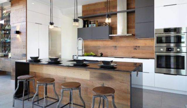 a modern space with an industrial feel and warm-colored wood on the backsplash and kitchen island