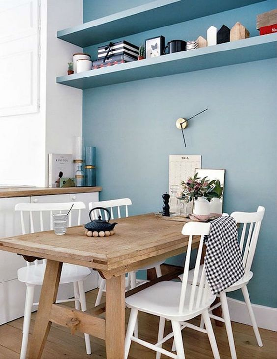 a serenity blue wall with a couple of shelves refreshes this dining nook and makes it cool