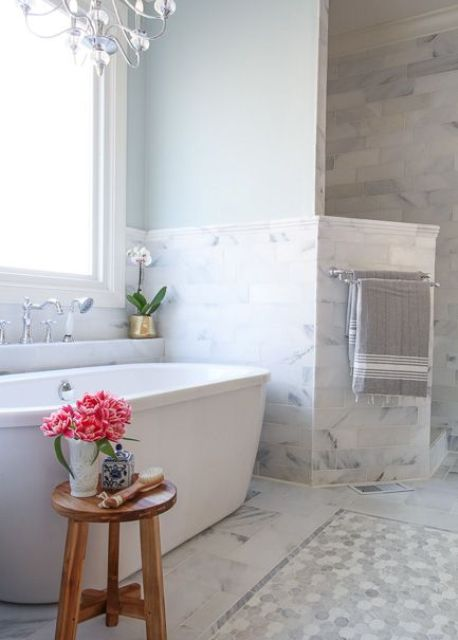 blue painted walls and grey marble tiles around the bathtub create a very peaceful look