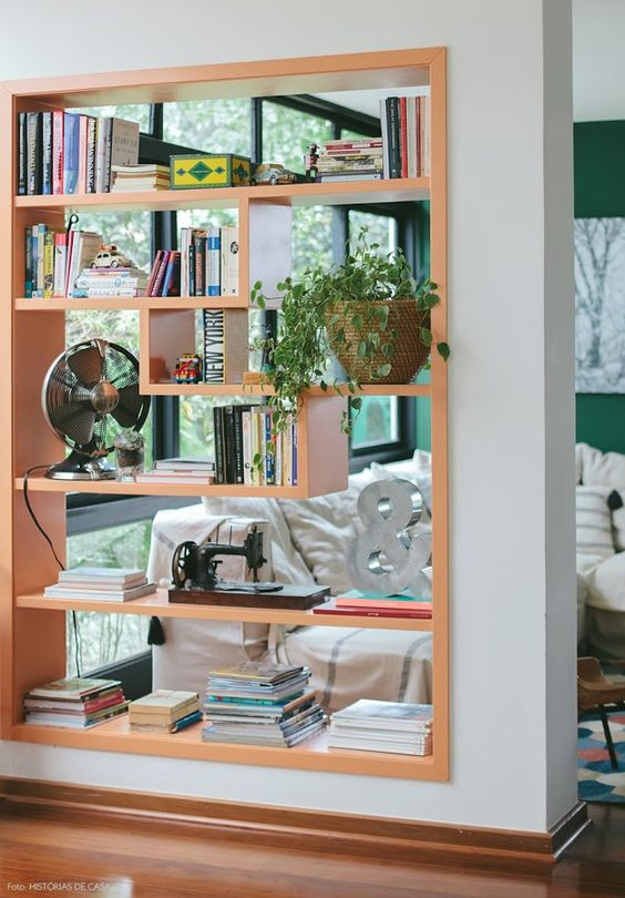 build in a shelving unit right into a wall, add a fun geometric shape to the shelves to delicately separate the spaces