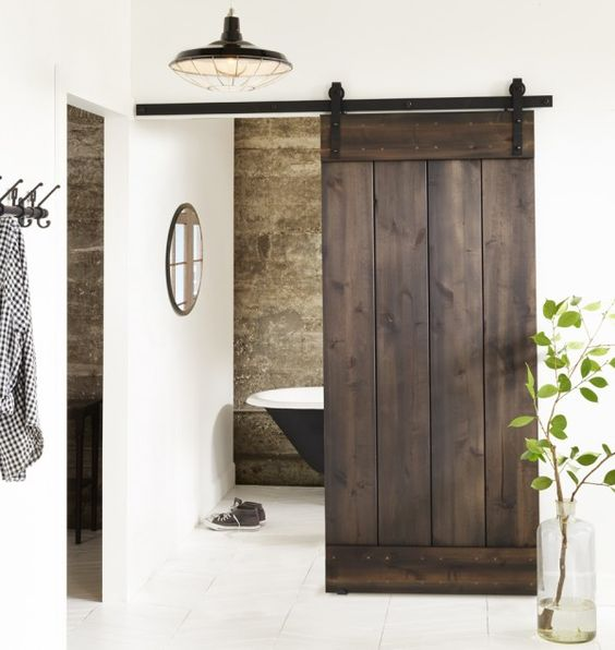 dark stained sliding barn door hides a small bathroom and stands out in a neutral space