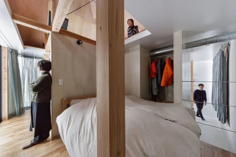 A small sleeping space and a makeshift closet are located next to the living space and can be divided with curtains