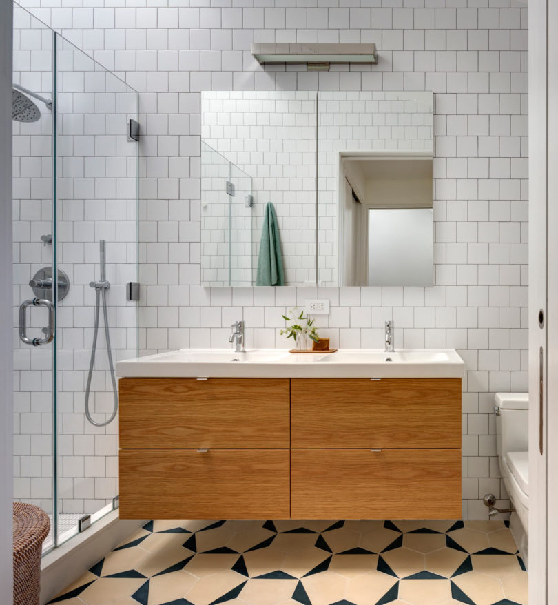 The bathroom is serene, with white tiles and a floating light colored wood vanity