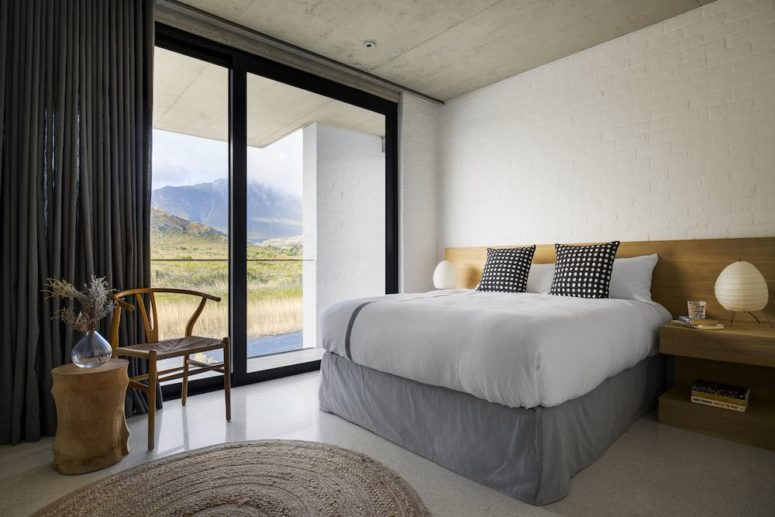 The master bedroom features a tall platform bed and floating nightstands plus gorgeous views