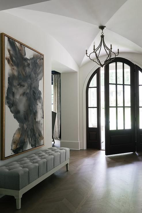 a modern entryway with a grey tufted bench and a creamy and grey artwork over it for a bold look