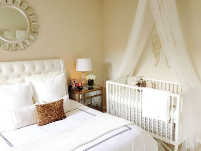 a modern glam master bedorom with a crib and a canopy by the wall - evena  small space can accomodate what you need