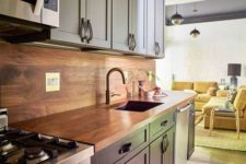 11 a navy and light blue kitchen with leather handles and a rich-colored plywood backsplash and countertop