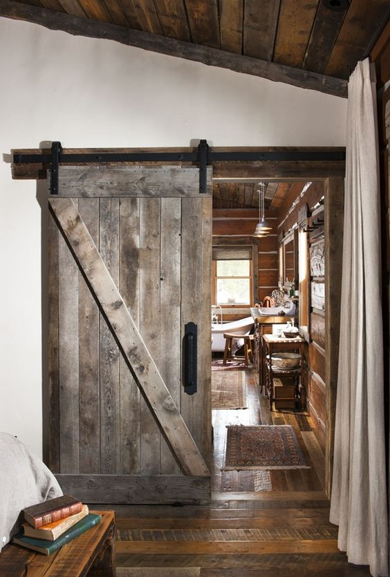 a sliding barn door of reclaimed wood is an ideal choice for a woodland or mountain cabin