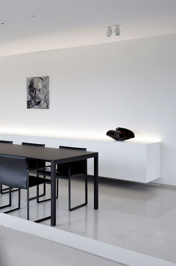 an ultra-minimalist space with a black dining set and a white floatign credenza with built-in lights