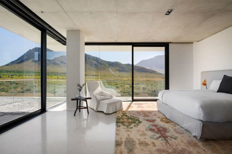 Panorama windows and sliding glass doors make this bedroom very special and conenct it to nature