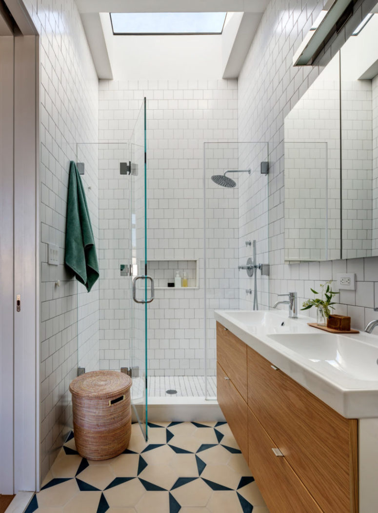 The shower space is done in white tiles with glass for a seamless look