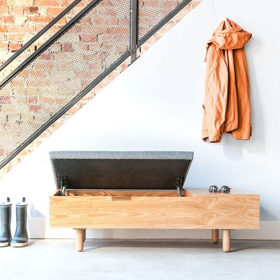 a comfy wooden storage bench with a grey seat on top and a space for accessories