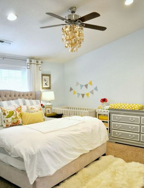 a modern farmhouse shared master bedroom and nursery space with a crib and a changing table