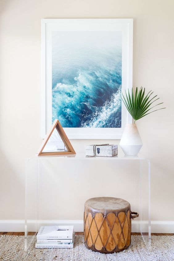 a modern oasis entryway, with an acrylic console, an ocean artwork and a drum