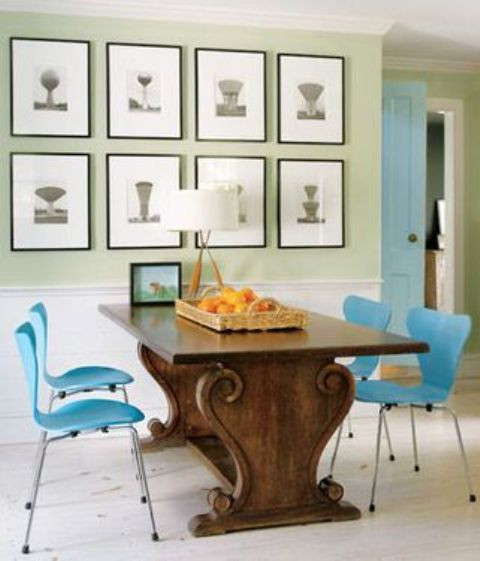 an antique table with carved legs and bold blue chairs on metal legs that highlight it
