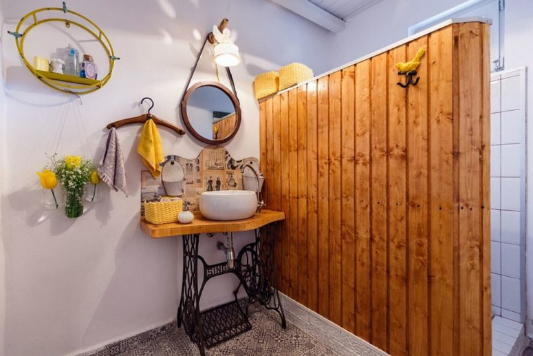 The bathroom features a natural wood space divider and a unique vanity of a sewing machine stand