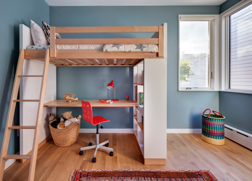 The kids' room is done in a creative way with a wooden bed up placed on shelving units and with a desk down