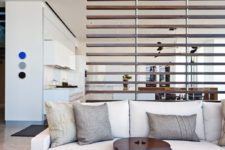13 a modern horizontal wooden plank screen lets light and air but divides the kitchen and the living room visually